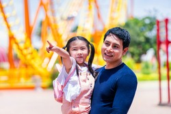 Father and daughter play at the amusement park. Family in theme park.