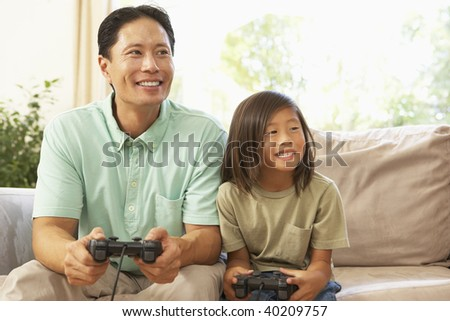 Father And Daughter Playing Computer Game At Home
