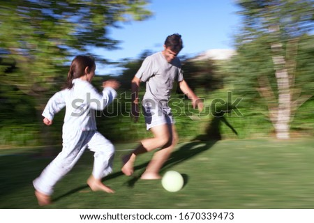 Father and daughter playing football in garden at home with action motion blur