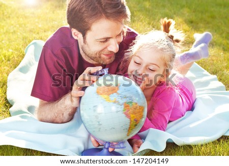 Father and daughter playing globe while laying outdoor on the grass in the garden during sunset
