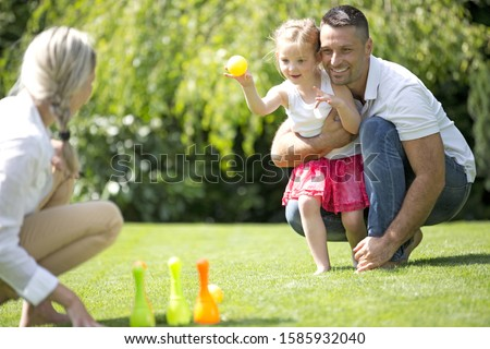 Father and daughter playing on lawn with skittles and ball