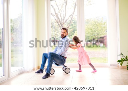 Father and daughter playing together, riding a bike indoors