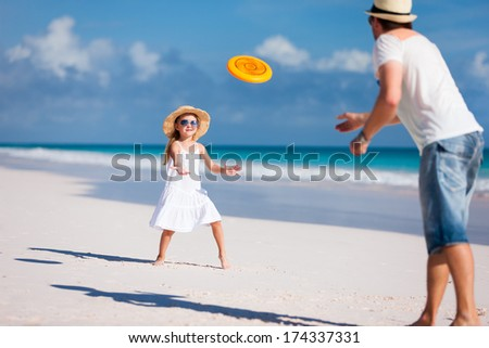 Father and daughter playing with flying disc at beach