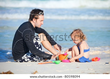 Father and daughter playing with toys at beach #80598094