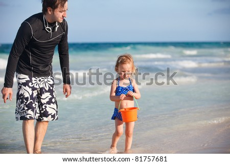 Father and daughter playing with toys at beach