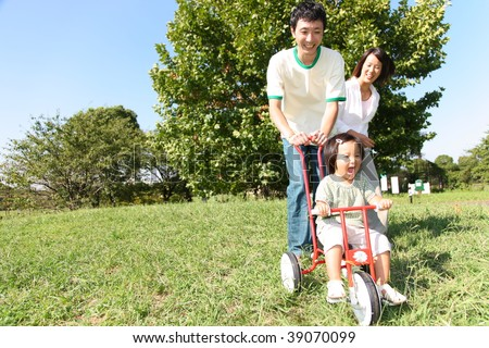Father and daughter plays with tricycle