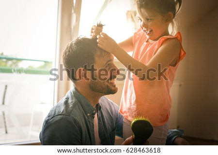 Father and daughter plying at home together. Girl is playing with her dad and says his hairstyle.
