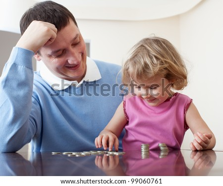 Father and daughter puts coins. Father teaches the child Finance