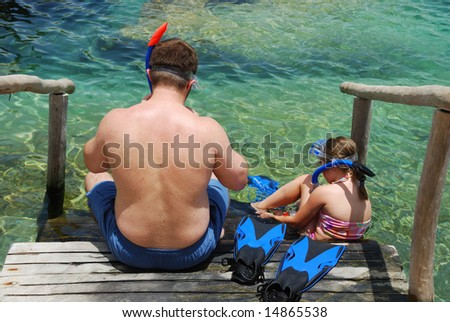 Father and daughter putting on snorkeling gear