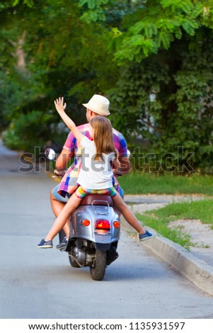 father and daughter riding a...