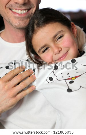 Father and daughter sat on sofa