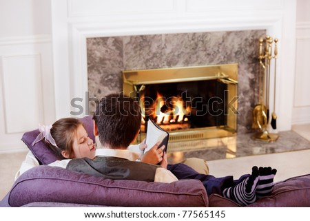 Father and daughter sit and read by the fire