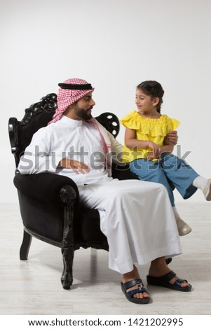 Father and daughter sitting on a couch.