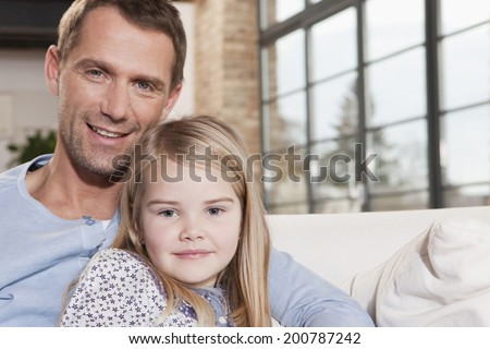 Father and daughter sitting on sofa embracing smiling close-up #200787242