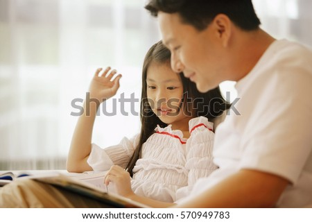 Father and daughter, sitting side by side, looking at book