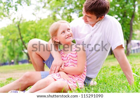 Father and daughter sitting together on the grass, and spend time with family