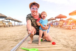 Father and daughter taking selfie on the beach - Cheerful dad and child playing outdoor on summer vacation day - Concept of family fun  moment using technology self photo for holiday joyful memories
