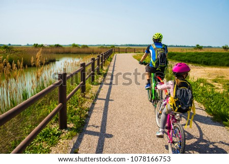 Father and daughter tandem going in bicycle. The bike itinerary FVG2 of Grado city, Friuli Venezia Giulia, region of Italy. Family, education, recreation and sport concept.