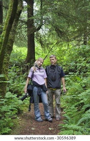 Father and Daughter walking through an old-growth Rainforest, Canada