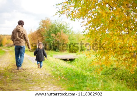 Father and daughter walking together in the park, fall day. Little girl and her dad exploring nature outdoors. Colorful autumn foliage. Copyspace