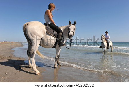 father and daughter with arabian and camargue horses on the beach. focus on the girl - stock photo