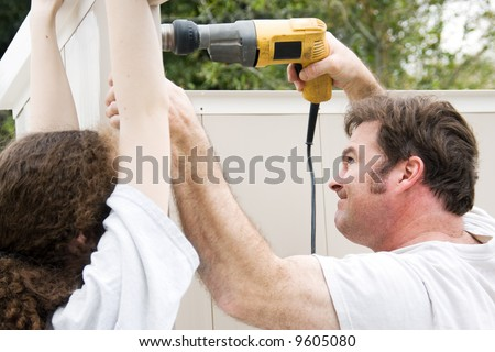 Father and daughter working on home improvement project.  He's using the drill.