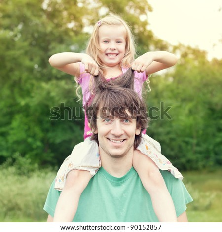 father and daughter.Young man holding blonde little girl on shoulders in park in summer