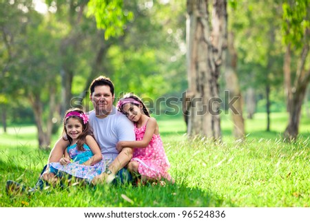 Father and daughters on picnic - hugging while sitting