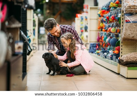 Father and dauther plays with puppy in pet shop #1032806458