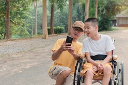 Father and Disabled child on wheelchair in the city park, They have fun with selfie by smart phone, Life in the education age of special children,Happy disability kid travel in family holiday concept.