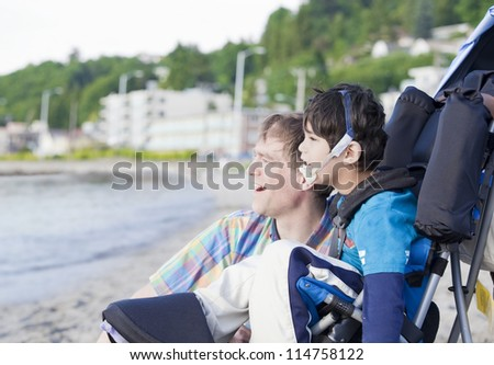 Father and disabled five year old son  on beach, looking out over water