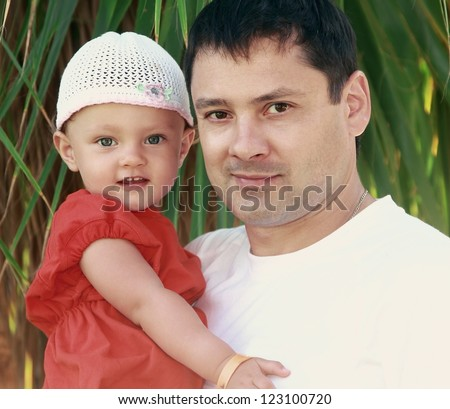 Father and happy baby girl on nature green background. Closeup portrait of love family