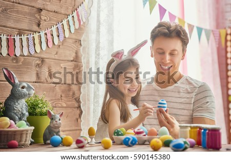 Father and his daughter are painting eggs. Happy family preparing for Easter. Cute little child girl wearing bunny ears. #590145380