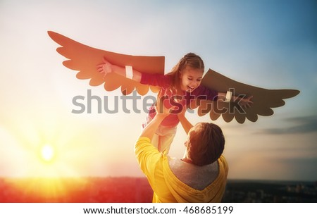 Father and his daughter child playing together. Little girl plays in the bird. Happy loving family having fun.