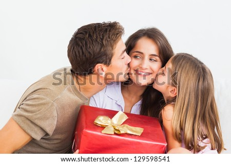 Father and his daughter offering a red gift and kissing