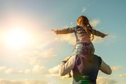 Father and his daughter playing outdoors. the child sits at the daddy on the neck, having lifted hands. against the sky in the sun. Happy loving family. Father's Day