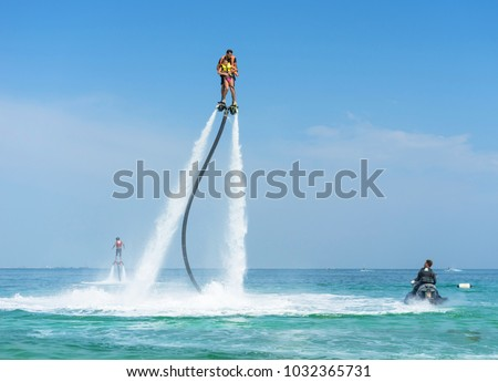 Father and his daughter posing at new flyboard at tropical beach. Positive human emotions, feelings, joy. Funny cute child making vacations and enjoying summer. #1032365731
