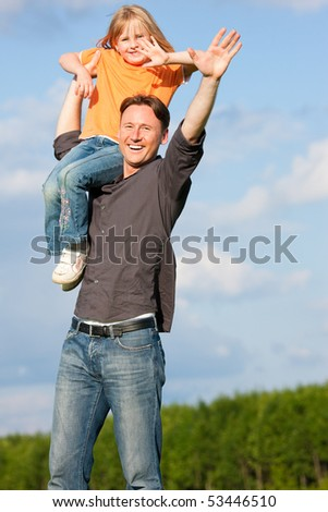 Father and his kid - daughter - playing together at a meadow, he is carrying her on his shoulders
