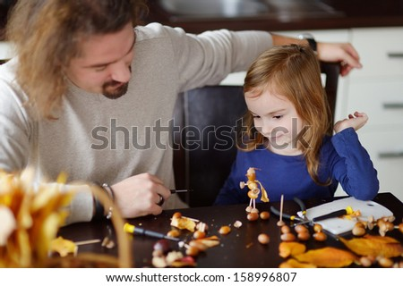 Father and his kid making chestnuts creatures together