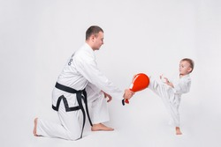 Father and his little boy practicing taekwondo over white background