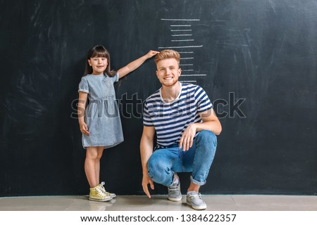 Father and his little daughter measuring height near wall with marks