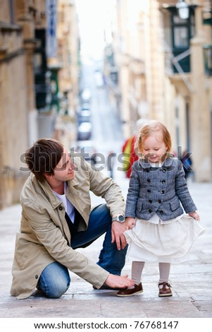 Father and his little daughter outdoors in city