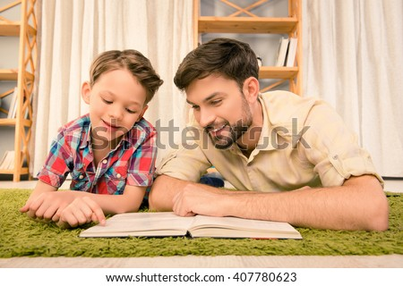 Father and his little son lying on carpet and reading books Foto stock ©