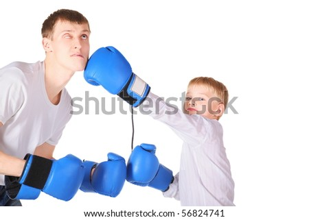father and his son is boxing with boxing gloves. boy is giving a slap to father's face.