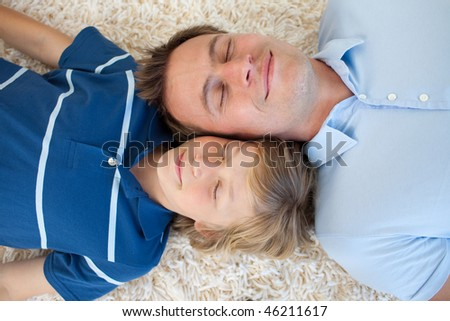 Father and his son lying on the floor with heads together