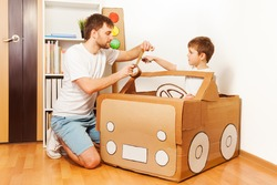 Father and his son making toy car of cardboard box