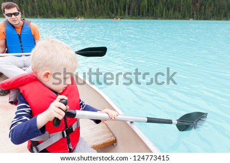 father and his son paddling on a canoe