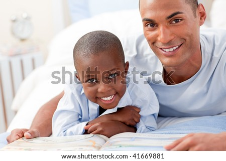 Father and his son reading on bed