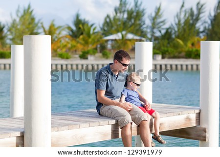 father and his son sitting together at the moorage