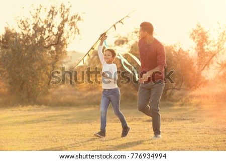 Father and his son with kite in countryside #776934994